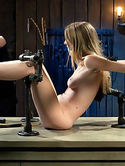 Ashley begins shackled to a wooden column. Her throat and wrists are locked down with cold...
