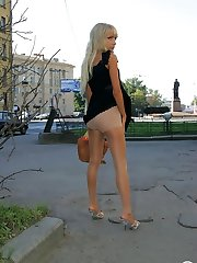Sexy blonde in extra shiny pantyhose playfully hiking up her skirt outdoors