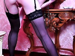 Dolled-up redhead smoothens her sexy FF nylons before some pussy fingering