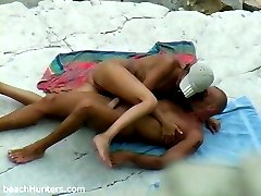 Horny nudist rides her bald lover on the sand
