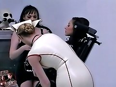 Domina in nurse latex uniform training pretty female slave in black latex suit