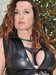 Leggy Milf Nylon Jane is outdoors posing in sexy black latex and silky nylon stockings