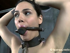 Sweet brunette chick stands with her hands up ready for bdsm play