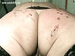Naked slave tied to workbench bdsm and back covered with candle wax gets spanked on her butt