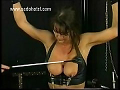 Tied up slave in leather got metal clamps on her big tits and large nipples by her masked master