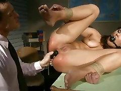 Beautiful brunette enjoys a BDSM game with a dildo
