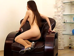 Small-breasted girl posing in a armchair