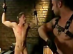 Muscle gay whips bound guy in dungeon