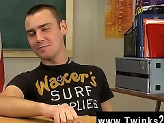 Twink movie Young brown-haired youngster Justin Giles sits at a desk in a