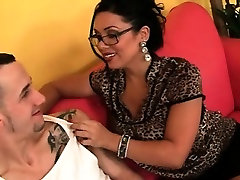 Busty cougar in glasses giving titjob on couch