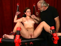 Full-figured brunette stands and attaches clamps to her own tits and pussy