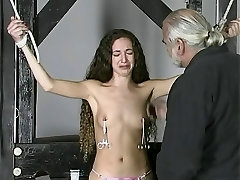 Slim brunette captive with small tits stands bound while dude clamps her tits